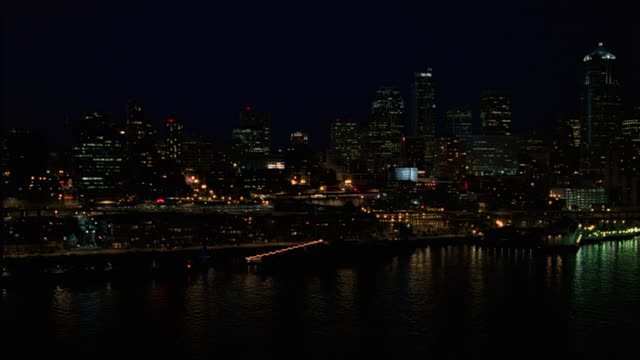 wide angle of seattle skyline. see lights from waterfront buildings, streets, and docks reflect off puget sound. multi-story buildings span frame. could be office buildings, high rises, skyscrapers, apartments, or condominiums. - puget sound stock videos & royalty-free footage