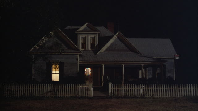 medium angle establish of two story farm house with grey roof and rectangular windows. see columns and porch. see white picket fence and illuminated lights inside house. - farmhouse stock videos & royalty-free footage
