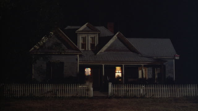 MEDIUM ANGLE ESTABLISH OF TWO STORY FARM HOUSE WITH GREY ROOF AND RECTANGULAR WINDOWS. SEE COLUMNS AND PORCH. SEE WHITE PICKET FENCE AND ILLUMINATED LIGHTS INSIDE HOUSE.