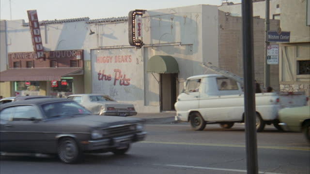 """MEDIUM ANGLE BUSY CITY STREET. SEE SIGN """"WILSHIRE CENTER"""" AT CORNER. SEE NIGHTCLUB ENTRANCE WITH SMALL GREEN AWNING OVER ENTRANCE. """"HUGGY BEAR'S THE PIT"""" PAINTED ON OUTSIDE OF BUILDING."""