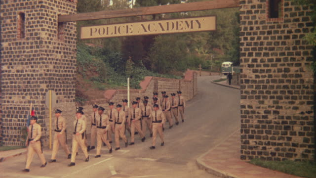 "vidéos et rushes de medium angle of road leading into police academy grounds. ""police academy"" sign hangs overhead. - officier grade militaire"