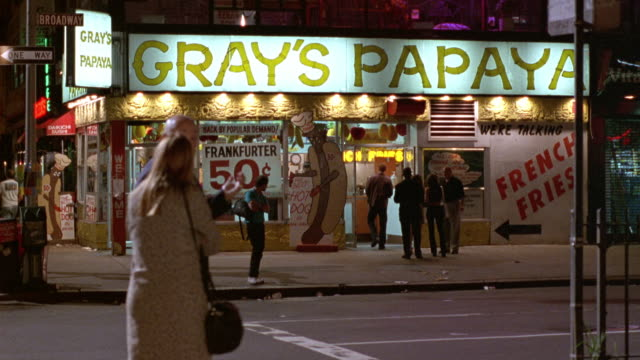 "medium angle of gray's papaya hot dog stand or restaurant at corner of broadway. see lit ""gray's papaya"" signs over building. - hot dog stock videos & royalty-free footage"