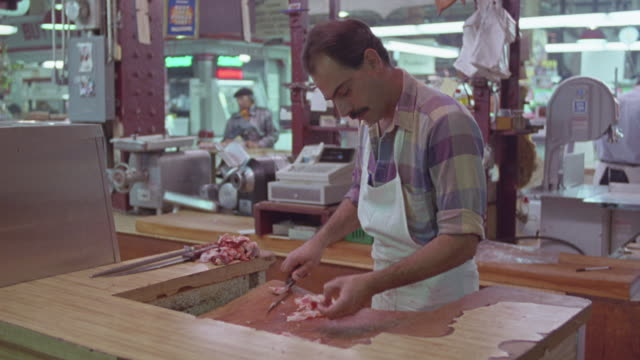 hand held of butcher carving meat inside deli or restaurant. move left, see people standing in line near glass case with food. people sitting at tables, man playing piano. - carving food stock videos and b-roll footage