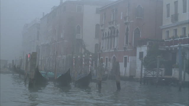 medium angle of venice canal with waterfront multi- story renaissance buildings and shops. see people unloading and boarding various small boats docked in front of buildings. - renaissance stock-videos und b-roll-filmmaterial