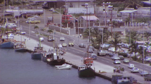 aerial of two way street running parallel with dock and parking lot. see house boats and ships docked along side of road. camera pans right and tracks yellow jeep moving down road towards pov. - parallel parking stock videos & royalty-free footage