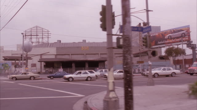 "stockvideo's en b-roll-footage met medium angle 3/4 side process plate passenger's side of town street in ghetto area in south central los angeles. pass by ""chevron"" gas station and destroyed liquor store after disaster or fire. - 1992"