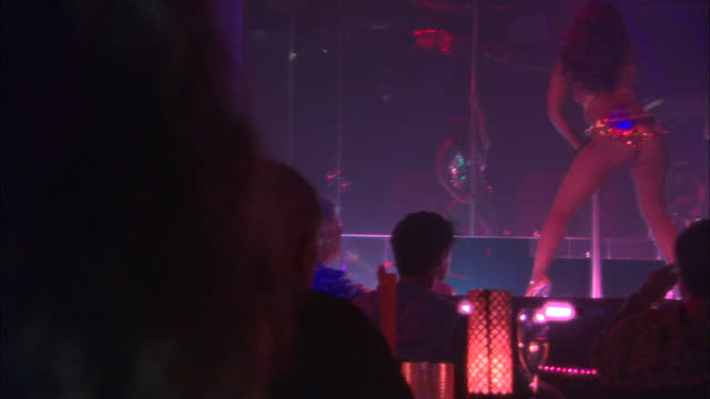 vidéos et rushes de medium angle of strip club. see audience of men and women in foreground. see flashing neon lights. see bikini-clad strippers or dancers dancing on stage with stripper poles in background. adult entertainment. - peep show