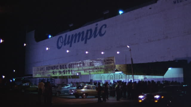 MEDIUM ANGLE OF  OLYMPIC AUDITORIUM IN DOWNTOWN LOS ANGELES. BUILDING HAS A SOLID, WINDOWLESS WALL APPROXIMATELY FOUR STORIES HIGH