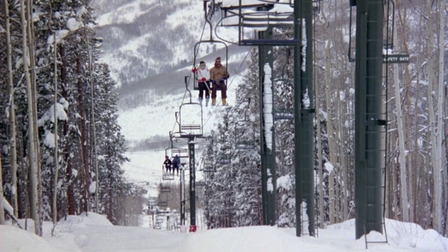 MEDIUM ANGLE OF SKI LIFT AT SKI RESORT. SEE LIFT CHAIRS ASCEND MOUNTAIN SLOPE WHICH IS COVERED IN SNOW. SEE TALL PINE TREES TO THE SIDE OF SKI LIFT AND SNOW COVERED MOUNTAIN SIDE IN BACKGROUND.