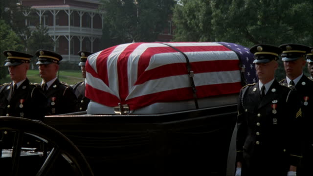 wide angle of caisson with eight army soldiers in dress uniforms on either side of carriage. see american flag draped over coffin. - funeral procession stock videos & royalty-free footage