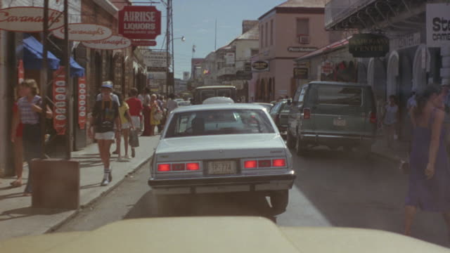 medium angle of one way street running between two rows of shops. pov from passenger seat following 1975 light blue american made sedan. see people walking in and out of shops and on sidewalks. see cars parked along right sidewalk. - following stock videos and b-roll footage