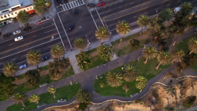 aerial of ocean blvd. in santa monica lined with  hotels, restaurants, office buildings and palm trees. traffic on street and cars parked on side of road. - santa monica blvd stock videos & royalty-free footage