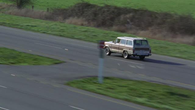 vídeos de stock e filmes b-roll de aerial view of white suv jeep wagoneer traveling down highway or freeway in countryside or rural area. flat fields and farmland in surrounding areas. farm houses. - jeep