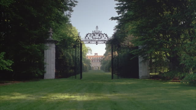 medium angle establish of black iron gates between two marble pillars. see large trees on either side. - old westbury stock videos and b-roll footage