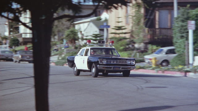 vidéos et rushes de pan left to right following black and white police car driving toward foreground on suburban street. - police
