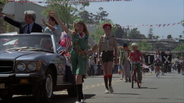 medium angle of parade down city street. see crowd lining sides of road. see clowns, man and women sitting on back of convertible mercedes, - western usa stock videos & royalty-free footage