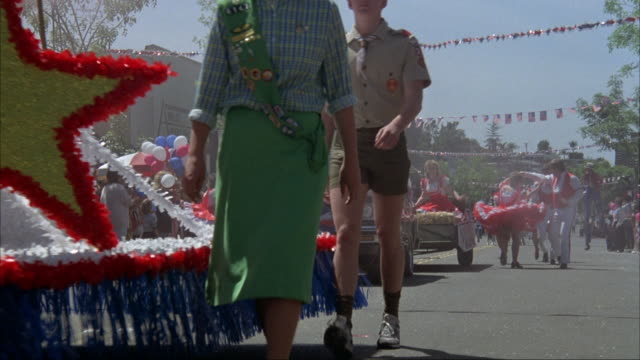 medium angle of parade down city street. see crowd lining sides of road. see clowns, man and women, baton twirler - fourth of july stock videos & royalty-free footage