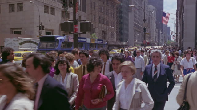medium angle of sunny city street and intersection in new york city. see crowds of people pedestrians walking and crossing traffic filled streets. - usa stock-videos und b-roll-filmmaterial
