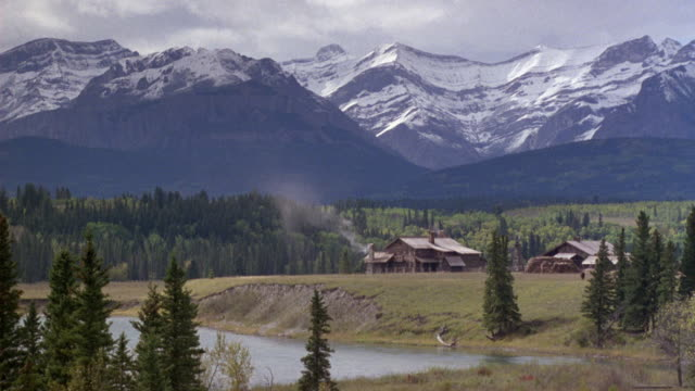 medium angle of two large wood cabins or ranch houses on large expanse of grassy land, fir trees and snowy mountains in background, river in foreground. - ranch home stock videos & royalty-free footage