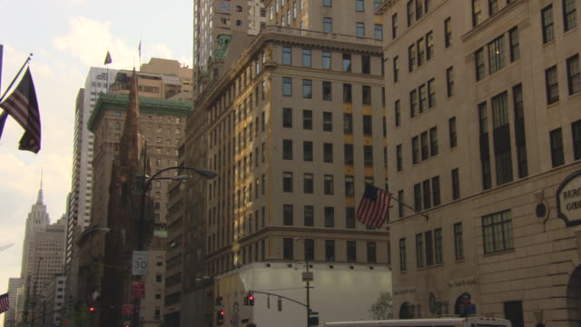 pull back from multi-story building to fifth avenue in manhattan. see bergdorf goodman store sign and american flag. - fifth avenue stock videos & royalty-free footage