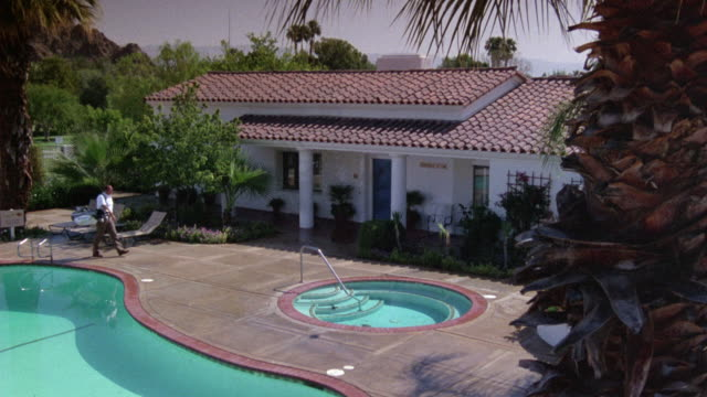 MEDIUM ANGLE DOWN OF GOLF COURSE COUNTRY CLUB HOUSE AND POOL. SEE RED TILE ROOF AND WHITE STUCCO WALLS OF CLUB HOUSE.