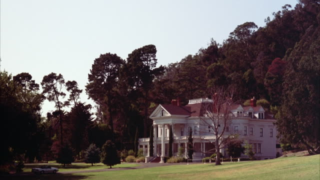 WIDE ANGLE OF DUNSMUIR ESTATE. WHITE, VICTORIAN, THREE-STORY UPPER CLASS HOUSE OR MANSION WITH COVERED PORCH AND WHITE COLUMNS.
