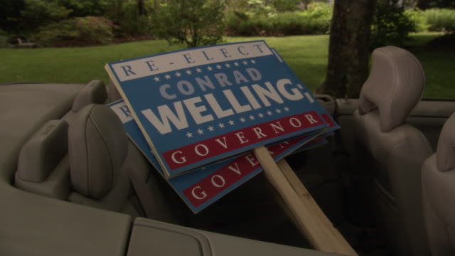 MEDIUM ANGLE OF SIGNS IN BACK SEAT OF CONVERTIBLE. SEE BLUE, WHITE AND RED SIGNS READING 'RE-ELECT CONRAD WELLING GOVERNOR'.