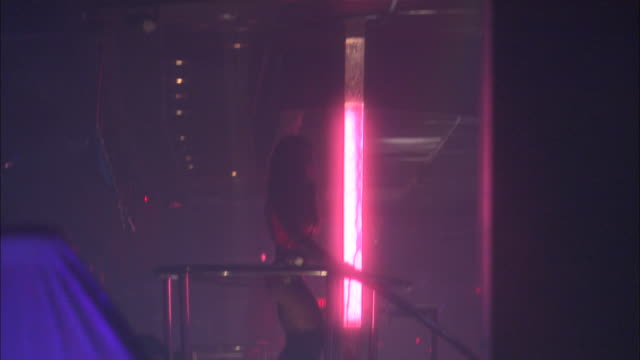 vídeos de stock, filmes e b-roll de medium angle of strip club interior. see topless or nude stripper wearing white boa walk into foreground and offscreen to left. - stripper