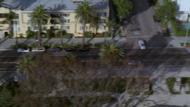aerial birdseye pov of hotels, restaurants, and office buildings on ocean blvd in santa monica near santa monica pier and beach. palm trees on either side of street. - santa monica blvd stock videos & royalty-free footage