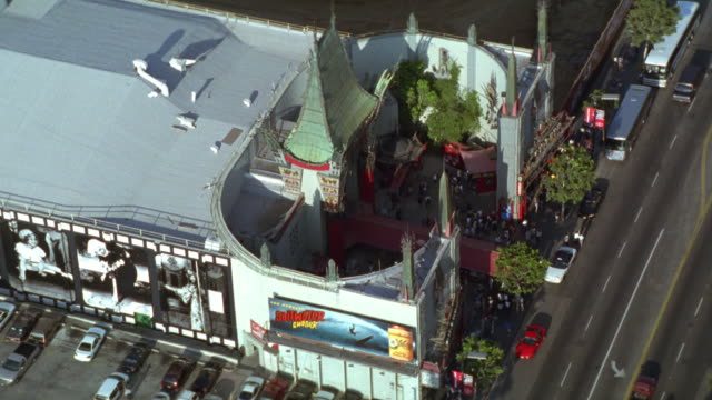 AERIAL OF MANN'S CHINESE THEATER ON HOLLYWOOD BLVD. HOLLYWOOD LANDMARK. RED CARPET AT ENTRANCE OF THEATER. PARKING LOT FULL OF CARS TO FRAME LEFT. TRAFFIC ON STREET. PEDESTRIANS WALK ON SIDEWALK. ROOSEVELT IN RIGHT FG.