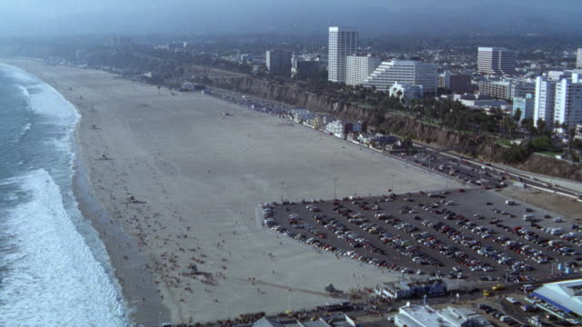 aerial view of ocean and city of santa monica. ferris wheels  and roller coaster on santa monica pier. beach or shore along cliff. - santa monica blvd stock videos & royalty-free footage