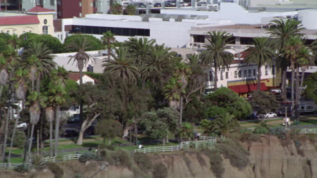 aerial view of hotels, restaurants, and office buildings on ocean blvd in santa monica. palm trees lines and blue sky. small cliff or bluff. cars drive on pacific coast highway near beach below. - santa monica blvd stock videos & royalty-free footage