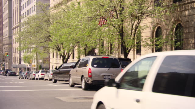 wide angle of black limo and taxis driving on one way avenue. see tall multi-story buildings. could be office buildings, hotels, high rises, or condominiums. - one way stock videos and b-roll footage
