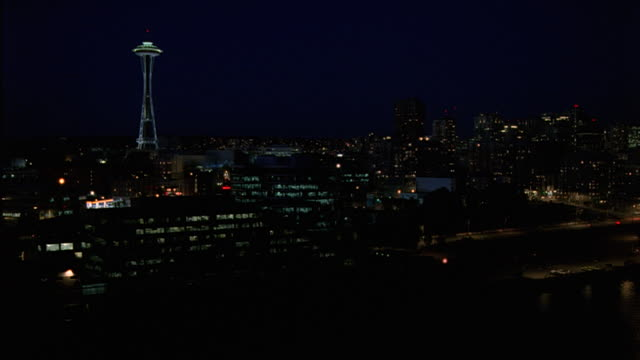 wide angle of space needle in seattle skyline. see lights from multi-story office buildings as cars pass on waterfront road. streets. downtowns. urban area. parking lot. puget sound. - space needle stock videos & royalty-free footage