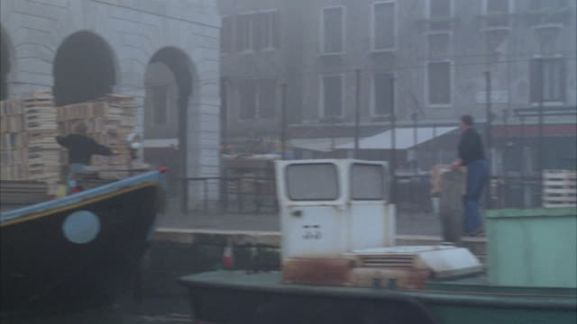 vídeos de stock e filmes b-roll de medium angle of venice canal with waterfront multi- story renaissance buildings and shops. see people unloading and boarding various small boats docked in front of buildings. - embarcação comercial