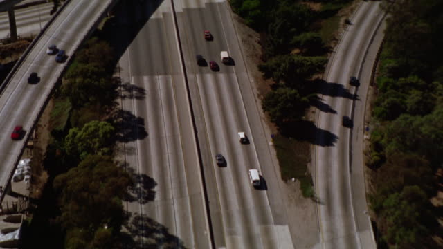 AERIAL OF 110 FREEWAY IN LOS ANGELES. SUBURBAN HOMES AND NEIGHBORHOODS. CARS DRIVING ON FREEWAY OR HIGHWAY. OVERPASSES.