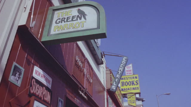 "UP ANGLE OF NIGHTCLUB. SEE SIGN ""THE GREEN PARROT"" ATTACHED TO RED BUILDING. SEE  SIGN ON FACE OF BUILDING ""NOW APPEARING SUGARPLUM"" AND LARGE SIGNS IN BACKGROUND ""COCKTAILS"" AND ""WESTERN BOOKS AND MAGAZINES"" ATTACHED TO DIFFERENT BUILDING."