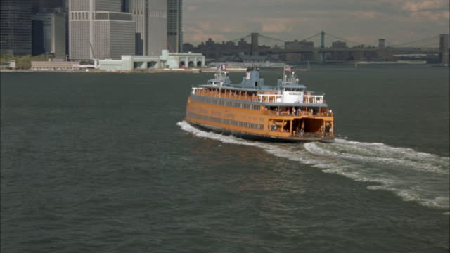 AERIAL TRACKING SHOT OF STATEN ISLAND FERRY,  NEW YORK BAY OR HARBOR. FERRY IS ORANGE. FERRY TRAVELS