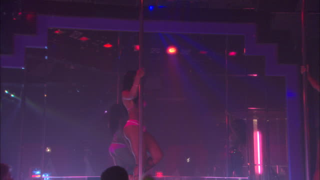 vidéos et rushes de wide angle of strip club. see men sitting at bar and bartender pouring alcoholic drinks in background. - peep show