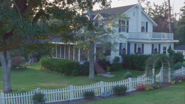pan down of middle class, two-story house. tree branches in fg partially blocking view of house. white picket fence and trellis on right side of house. - zweistöckiges wohnhaus stock-videos und b-roll-filmmaterial