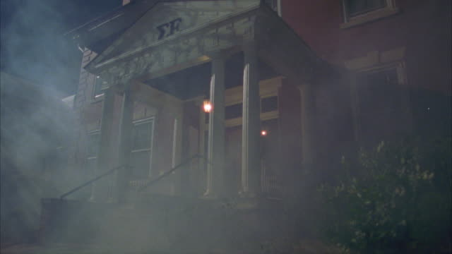 up angle of two story brick sigma epsilon fraternity house with white columns and porch. hanging light above entrance is on, swings gently. fog, mist. - brick house stock videos & royalty-free footage