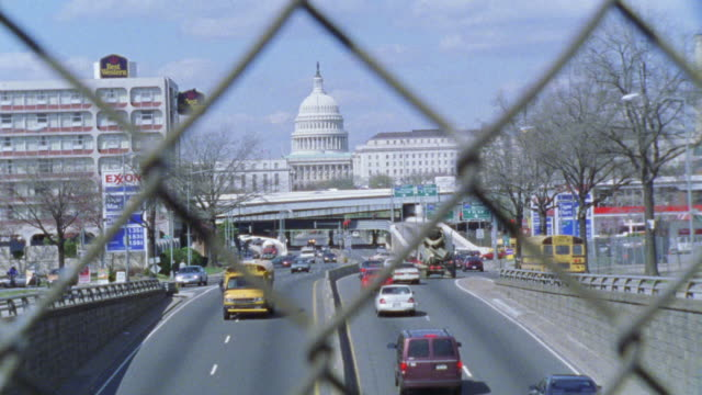wide angle of cars driving on freeway and capitol building in bg as blue ford sedan exits expressway or freeway. chain link fence in fg. - exxon stock videos & royalty-free footage