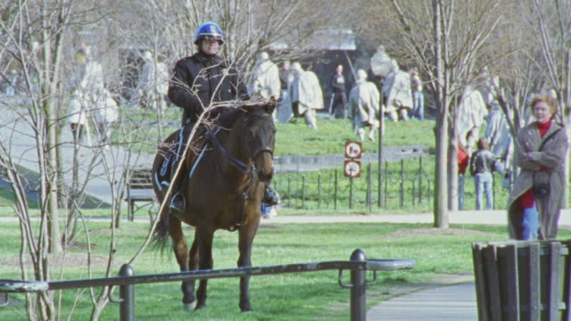 stockvideo's en b-roll-footage met medium angle of a mounted police officer riding through park, national mall. korean war veterans memorial visible in bg. three teenagers approach officer and pet horse. - memorial