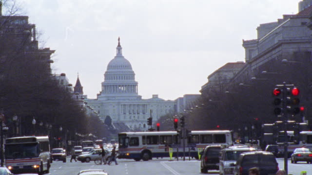 HAND HELD OF CAPITOL HILL. SEE ONGOING TRAFFIC IN FRONT OF BUILDING. CARS AND BUSES. DOMED GOVERNMENT OFFICE BUILDING.