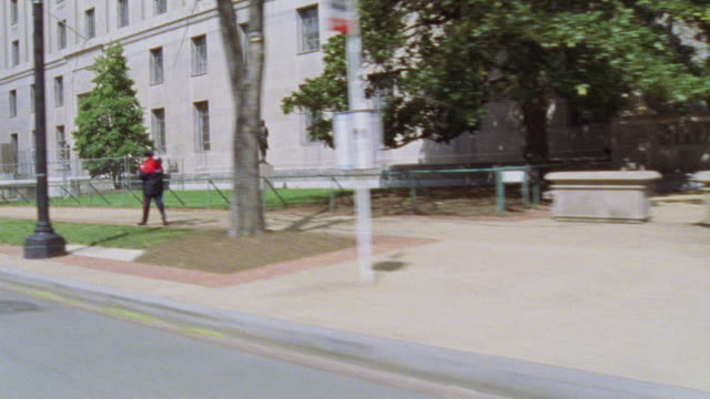 MEDIUM ANGLE DRIVING POV LEFT OF DEPARTMENT OF JUSTICE BUILDING. CAMERA MOVES FROM L-R ALONG THE SIDE OF THE BUILDING.