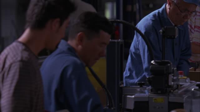 stockvideo's en b-roll-footage met medium angle of men working in bottling plant or factory. employees stand next to conveyor belt, packing bottles of juice into cardboard boxes. - men