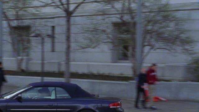 vídeos de stock e filmes b-roll de hand held driving pov following chrysler sebring car turning right at light. pans up to building. chrysler car. city streets. high rise government office buildings. - prédio chrysler