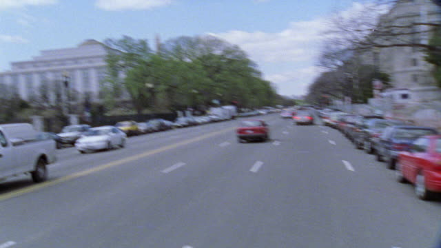 stockvideo's en b-roll-footage met wide angle moving pov from top of car driving down city street, pov makes u-turn then passes national archives building, government buildings. cars driving on street. intersections. justice building. - national archives washington dc