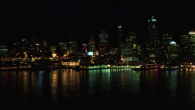 wide angle of downtown seattle skyline. see light from docks and waterfront buildings reflect off puget sound. could be ferry boat terminal. skyscrapers, high rises, multi-story office buildings. urban area. - puget sound stock videos & royalty-free footage