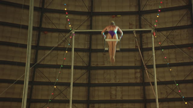 medium angle of female trapeze artist swinging on trapeze. see her hang upside-down with arms outstretched, male trapeze artist enters top frame. - zirkusveranstaltung stock-videos und b-roll-filmmaterial